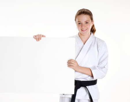 Martial arts girl holding a white panel.karate girl portrait holding a panel.Martial arts and karate kid portrait.