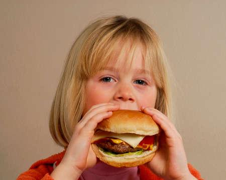 어린 소녀: Little girl eating hamburger.