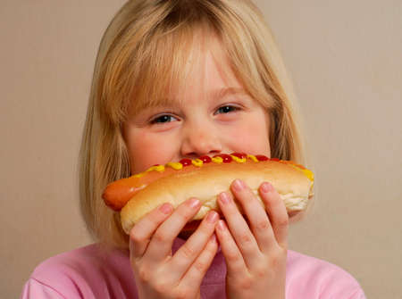 provocative food: Little girl eating a hot dog.Kid eating hot dog.