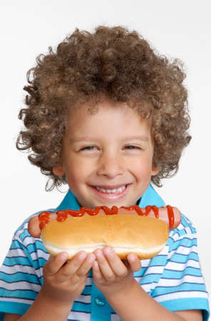 perro comiendo: Niño que come el perrito caliente, Kid celebración de perro caliente.