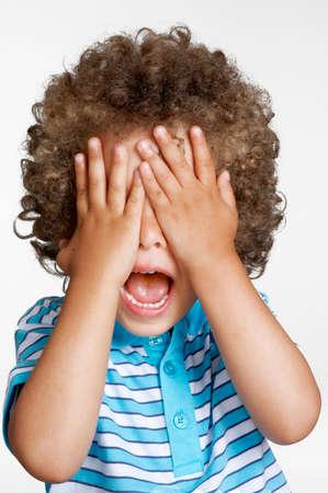 surprised kid: Expressive surprised kid covering his eyes. Stock Photo