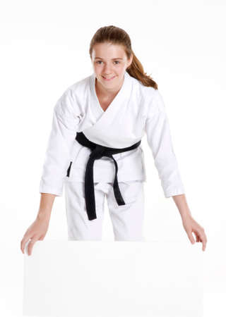 Martial arts girl holding a white panel.karate girl portrait holding a panel.Martial arts and karate kid portrait. photo
