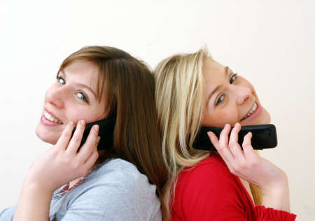 Two young women talking together on cell phone. Stock Photo