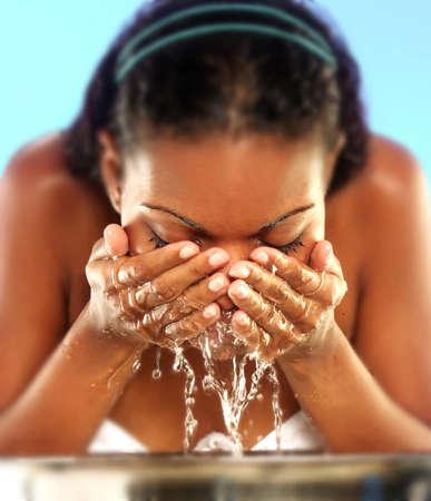 jabon: Mujer afroamericana joven lavando la cara.