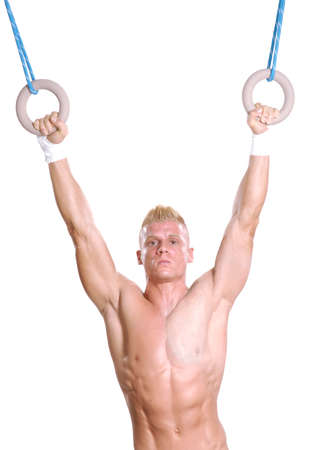 young man: Young man holding two rings.Gymnastic on rings. Stock Photo