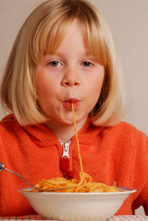 eating pasta: Funny young girl eating pasta.