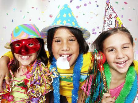 personas festejando: Tres niños divertidos carnaval retrato disfrutando juntos. Foto de archivo