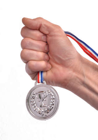 silver medal: Award winner hand holding a silver medal isolated on white background.