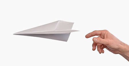 plane landing: Hand throwing paper plane isolated on white background.