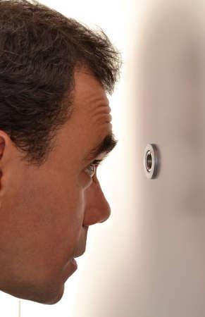 cerrar la puerta: Hombre joven feliz sorprendido mirando a través de la mirilla de su puerta principal. Foto de archivo