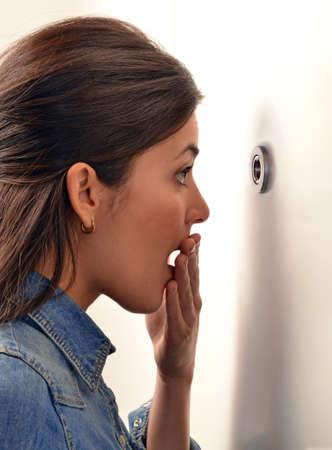 surprised: Mujer joven sorprendida mirando a través de la mirilla de su puerta principal.