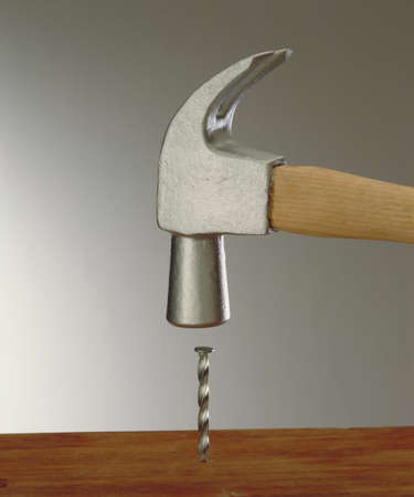 hammering: Hammering a nail on wood table