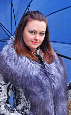 presentiment: Fashion style young woman holding a big blue umbrella.