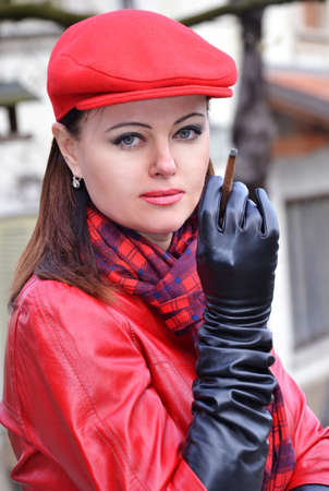 red hat: Fashion style woman smoking wearing red hat,black gloves and red leather jacket.