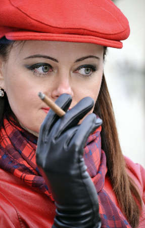 Fashion style woman smoking wearing red hat,black gloves and red leather jacket.