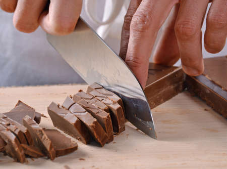 Cook hands cutting chocolate bar with a kitchen knife on cutting board.