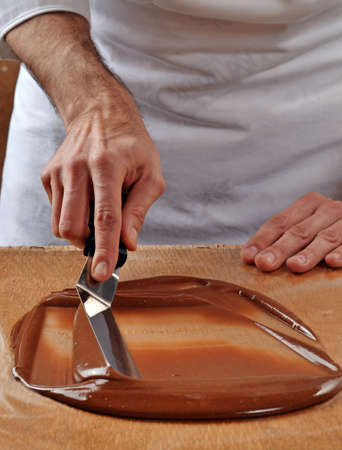 cook: Cook mixing chocolate cream with professional chocolate spatula. Melted dark chocolate. Stock Photo