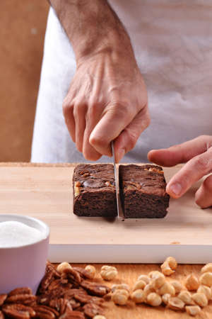provocative food: Pastry chef hands preparing and slicing fresh chocolate brownies on cutting board