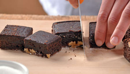 provocative food: Pastry chef hands preparing and slicing fresh chocolate brownies on cutting board. Stock Photo