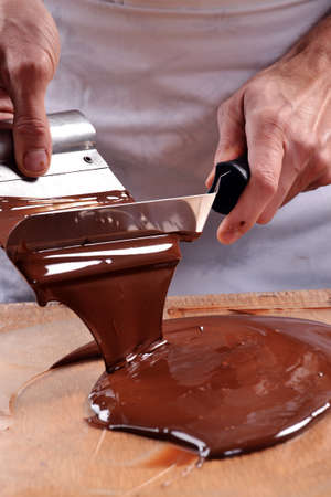 pastry chef: Cook mixing chocolate cream with professional chocolate spatula.