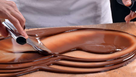 provocative food: Cook mixing chocolate cream with professional chocolate spatula. Melted dark chocolate. Stock Photo