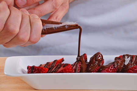provocative food: Adding dark chocolate cream on strawberries. Chocolate syrup on strawberries.