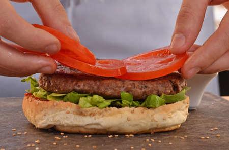 haciendo pan: Cocine la adici�n de tomate en hamburger.Preparing y hacer hamburguesas. Foto de archivo