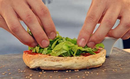 cocineros: Cocine añadiendo lechuga en burger.Preparing hamburguesa.