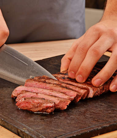 provocative food: Cook slicing grilled beef steak on stone board. Stock Photo