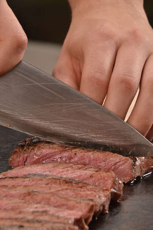 animal blood: Cook slicing grilled beef steak on stone board. Stock Photo