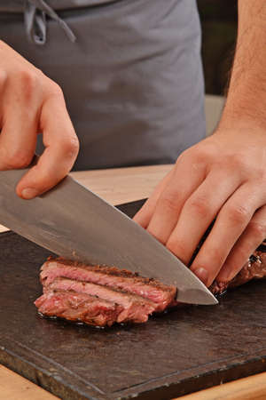 provocative food: Cook slicing grilled beef steak on stone board