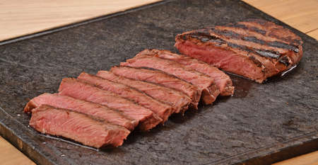 provocative food: Sliced grilled beef steak on stone board.