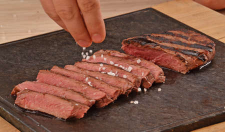 provocative food: Cook seasoning grilled beef steak on hot stone.adding salt. Stock Photo