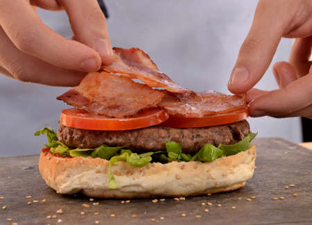 provocative food: Cook preparing burger adding bacon. Stock Photo