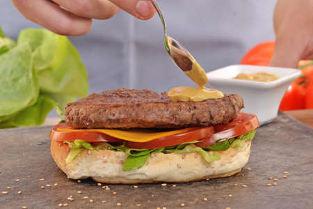 provocative food: Cook adding sauce on burger