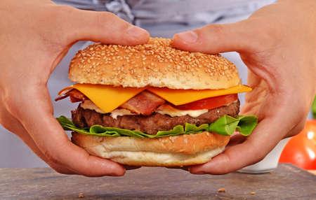 fast food: Cocine las manos que sostienen y la preparaci�n de la hamburguesa Foto de archivo