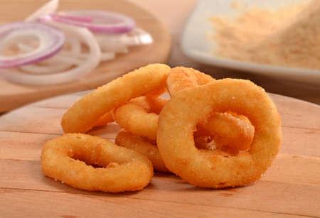 onion: aros de cebolla en la mesa de madera y los ingredientes