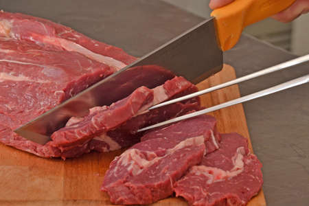 provocative food: Cutting a piece of fresh meat, cutting meat