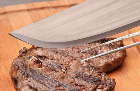 provocative food: Cook slicing grilled beef steak on wood board.