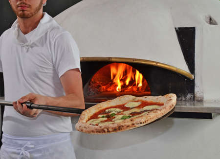 cook out: Cook taking out baked  pizza from oven