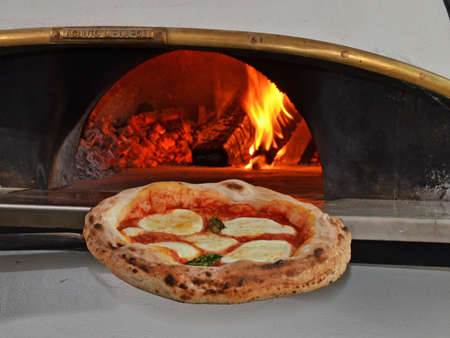 margarita pizza: Cook taking out baked margarita pizza from oven Stock Photo