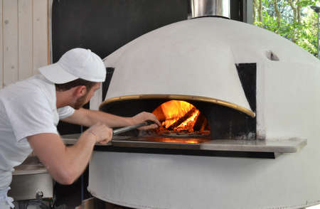 Pizza man portrait.baker man cooking pizza on traditional wooden oven