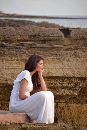 nostalgic: Nostalgic serene woman on white dress sitting on rocks looking at the sea sunset.