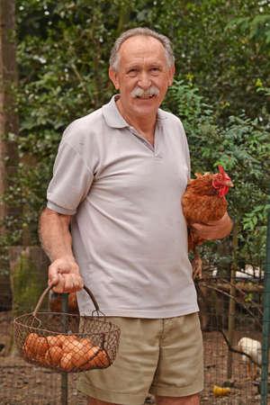 gallina con huevos: Happy farmer holding a brown hen and egg basket.