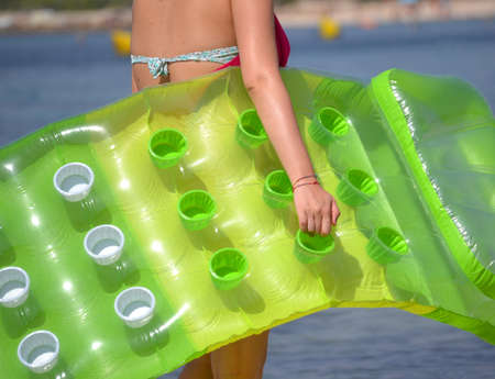 inflate: walking to to the beach holding an air mattress,inflate bed.