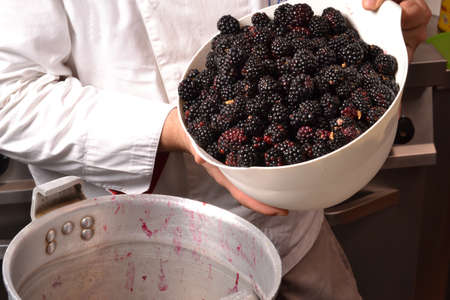blending: Cook preparing brewing and blending blackberry cream for jam. Stock Photo