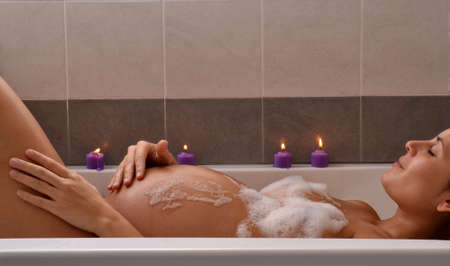 Serene pregnant woman in relaxing candle ambient at bathtub before give Birth. Beautiful young pregnant woman at beauty salon spa getting a body treatment.