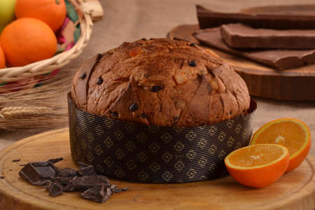 provocative food: Orange panettone bread and ingredients on rustic wood ambient.Panetone and ingredients.Traditional italian christmas food. Stock Photo