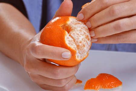 peeling: Hand peeling tangerine fruit.