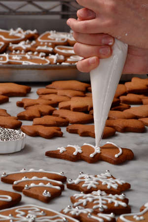 christmas baker's: Pastry chef hands preparing christmas cookies holding a vanilla cream cone. Stock Photo